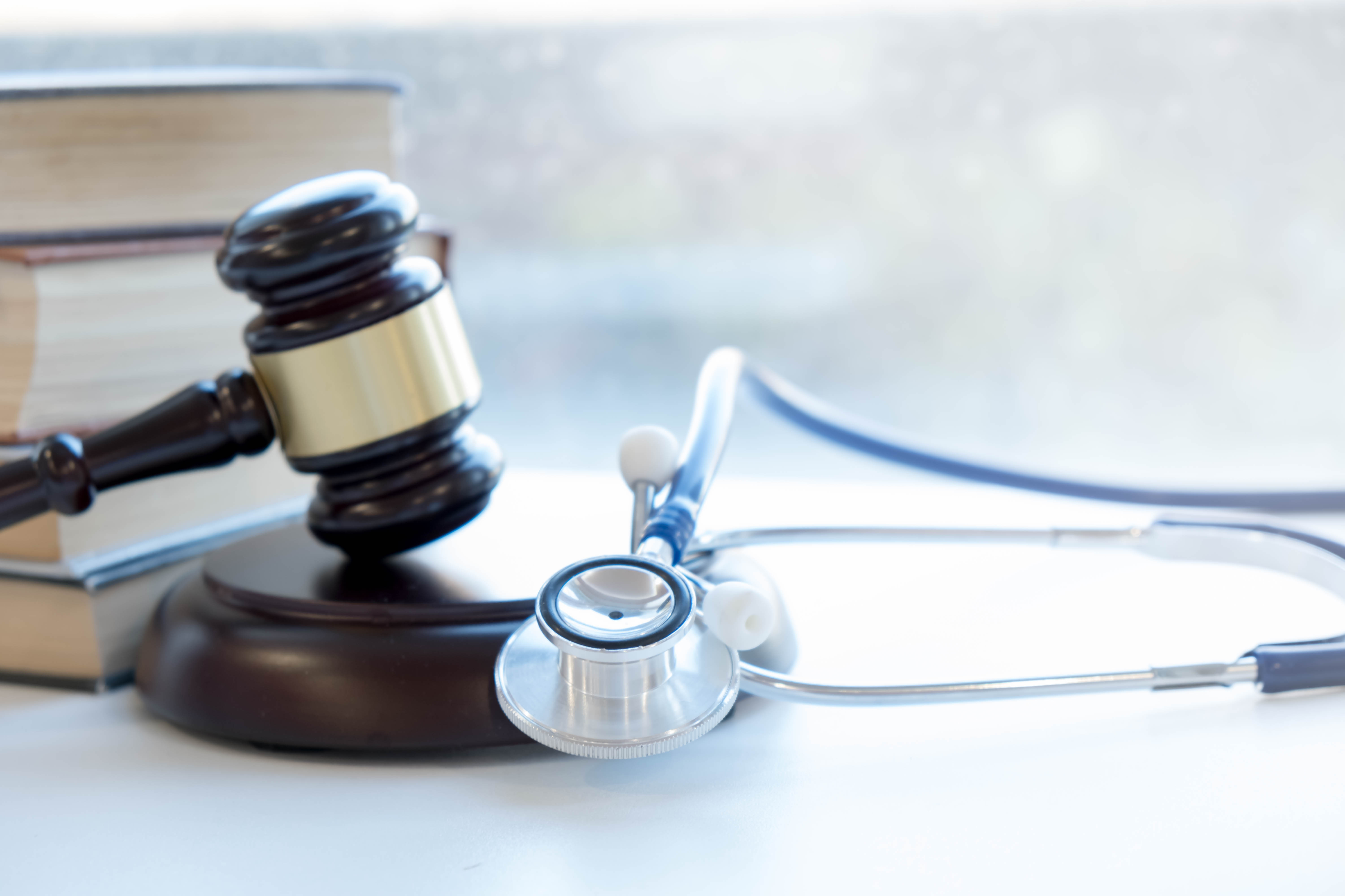 Gavel and stethoscope and a stack of books